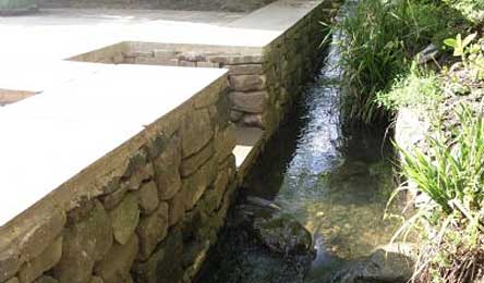 Dry stone retaining wall by stream